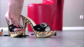 Sexy slender amateur dominatrix in high heels crushes toys
